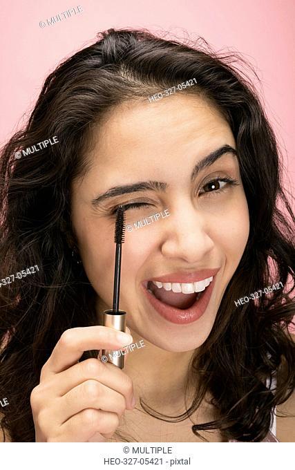 Close up portrait brunette Latina woman applying mascara against pink background
