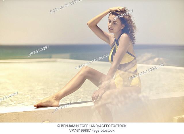 woman sitting at pool, holiday, summer, sexy, bikini, swimwear, curly hair