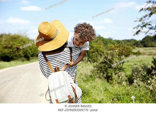 Mother with son walking on country road