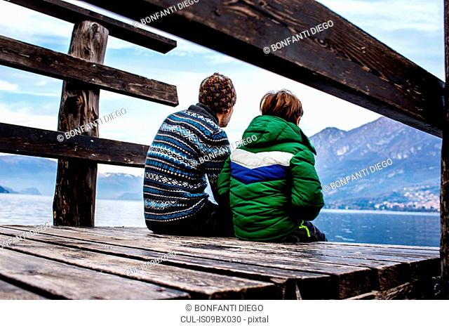 Boy and father sitting on lakeside pier, rear view, Lake Como, Onno, Lombardy, Italy