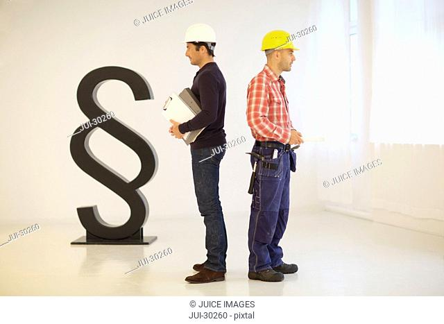 Architect and construction worker on job site,  paragraph sign in background