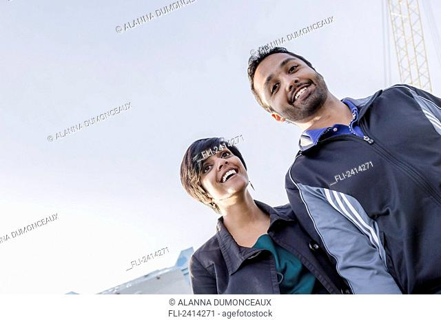 A young Indian ethnicity couple walking together smiling and laughing; Victoria, Vancouver Island, British Columbia