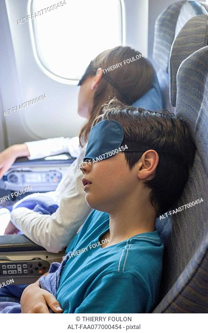 Children sleeping on airplane, wearing sleeping masks