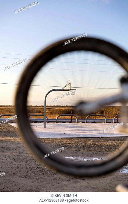 The Alakanuk Public School Basketball Court as seen through the wheel of a bicycle, Alakanuk, Yukon Delta, Arctic Alaska, USA, Fall