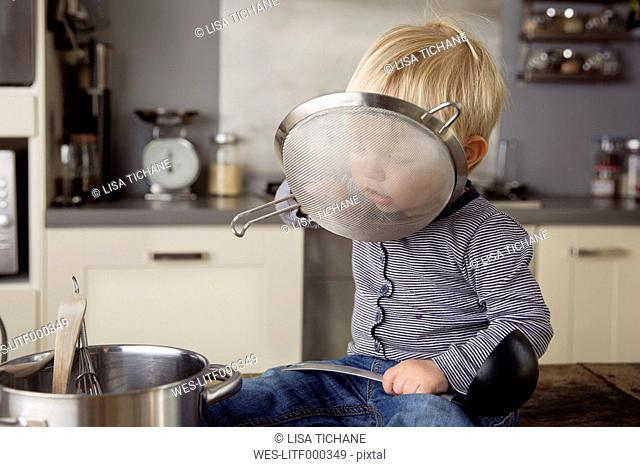 Portrait of toddler boy sitting on the kitchen table playing with strainer