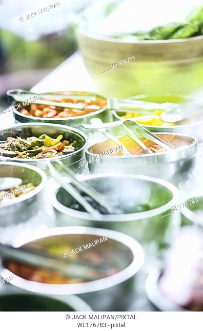 bowls of mixed fresh organic vegetables in modern salad bar display