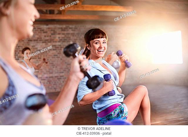 Smiling young women with dumbbells in exercise class gym studio