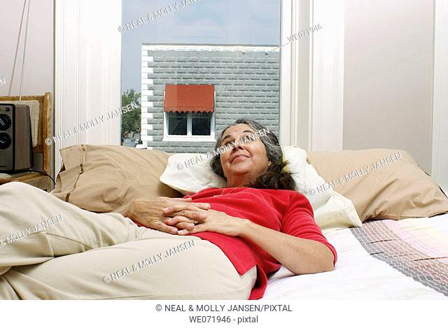 Elderly woman rests comfortably on bed by window