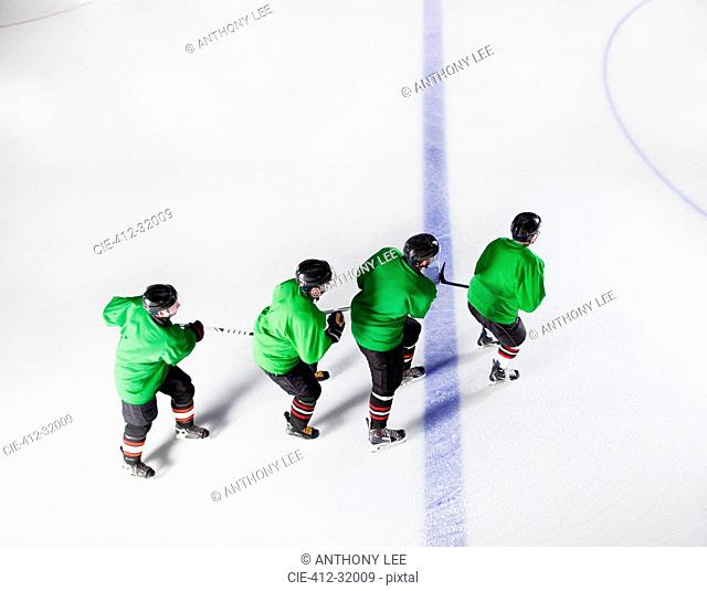 Hockey team in green uniforms skating in a row on ice