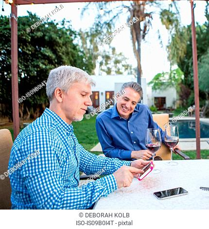 Two mature men looking at smartphone touchscreen at garden party table