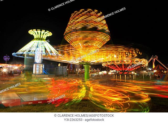 Colorfully illuminated rides, including the Sizzler in the foreground, spin against the night sky during the New Jersey State Fair on August 13