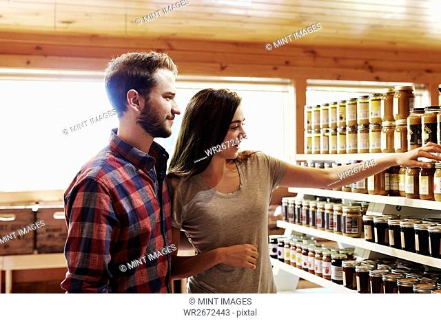 A young man and woman choosing from a display of canned produce in a farm shop