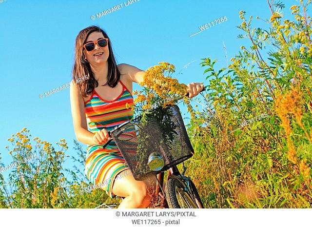 A pretty, young woman on a bike with wildflowers in the meadow