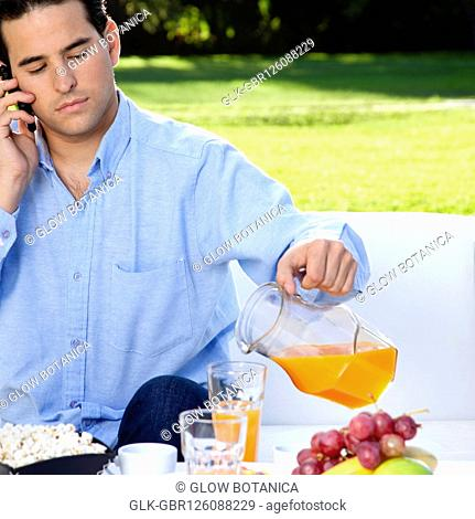 Man talking on a mobile phone while having breakfast