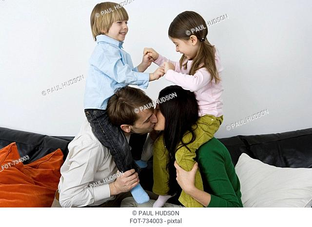 Two parents carrying children on their shoulders and kissing