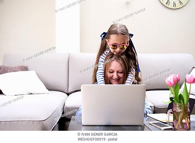 Portrait of smiling mother and little daughter using laptop in the living room