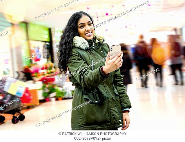 Young woman taking selfie in shopping mall