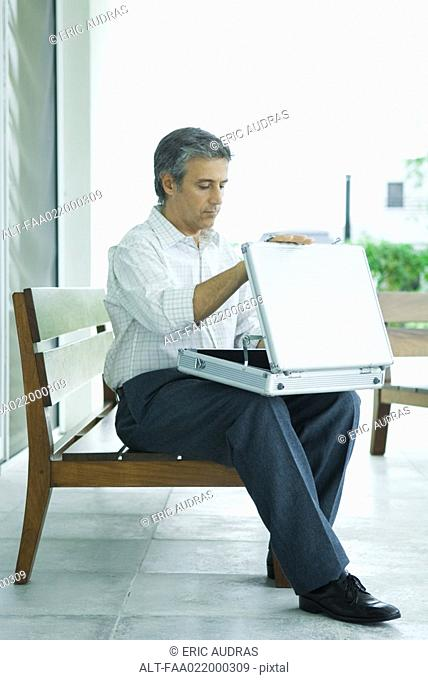 Mature man sitting on bench, opening briefcase, full length