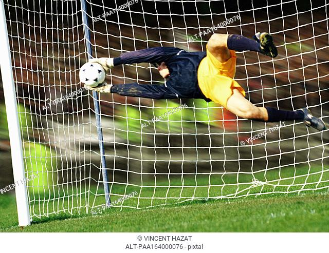 Goal keeper, horizontal, saving ball during match, full length