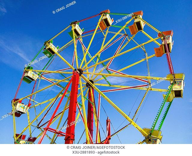 A Ferris wheel at a funfair against a blue sky