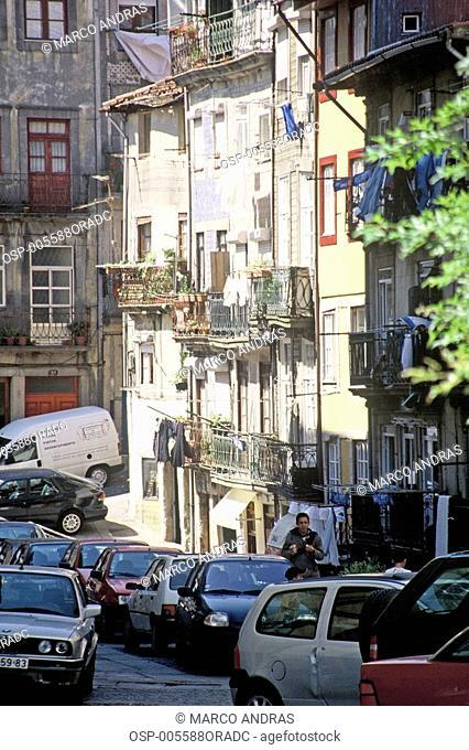a narrow street full of cars at portugal