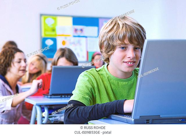 Portrait of boy working at laptop in class