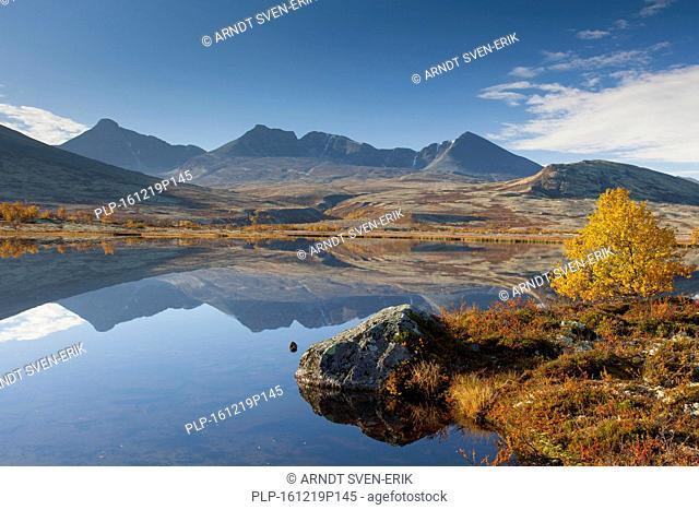 Digerronden reflected in water of lake in autumn, Døråldalen in Rondane National Park, Oppland, Norway