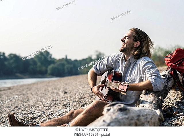Exuberant young man sitting at the riverside playing guitar