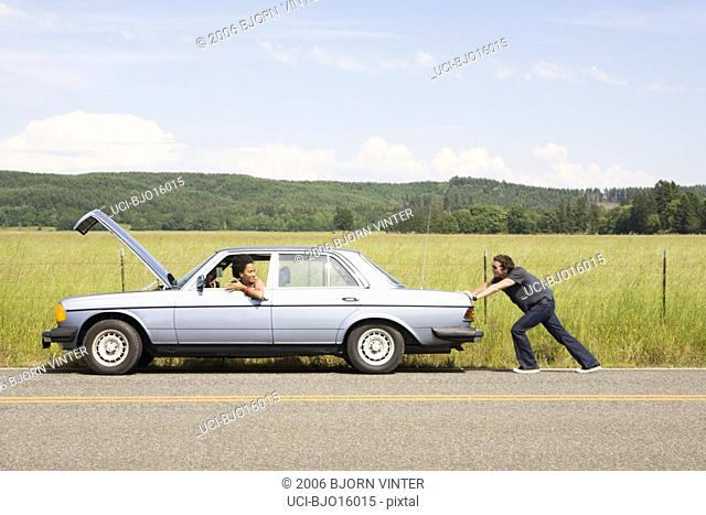 Man pushing broken down car