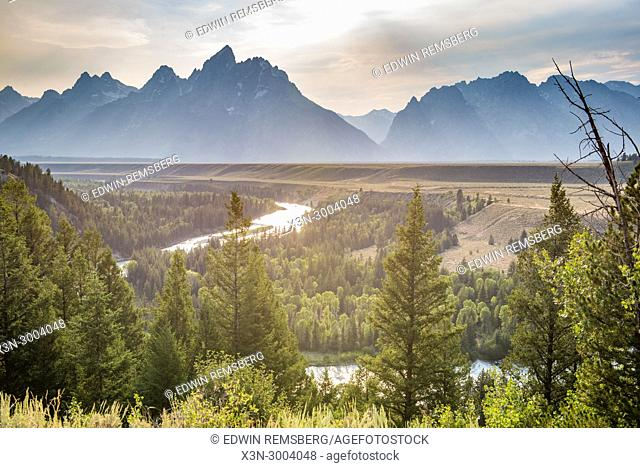Snake River overlook shows Teton Mountain Range looming over illuminated forest and Snake River at dusk, Grand Tetons National Park, Teton County, Wyoming