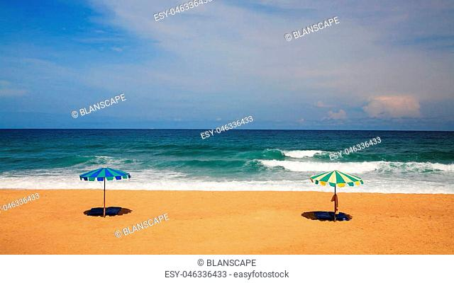 Two parasol or umbrella on a sunny day, sea in background. Vacation or Holiday symbol