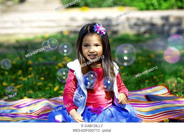 Little girl outdoors surrounded by saop bubbles