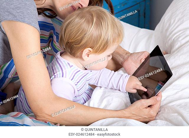 eighteen month aged blonde baby with brunette woman mother reading digital tablet on white bed