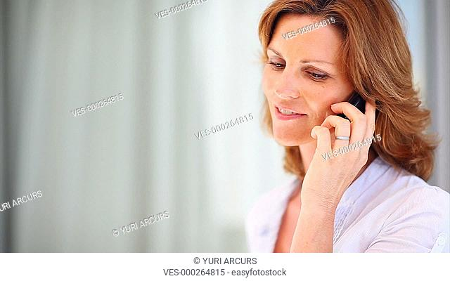 Pretty woman taking a casual phone call and giving you a smile