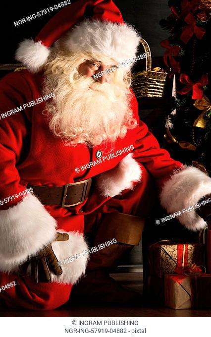 Santa placing gifts under Christmas tree in dark room