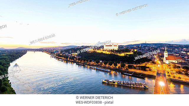 Slovakia, Bratislava, cityscape with river cruise ships on the Danube at evening twilight