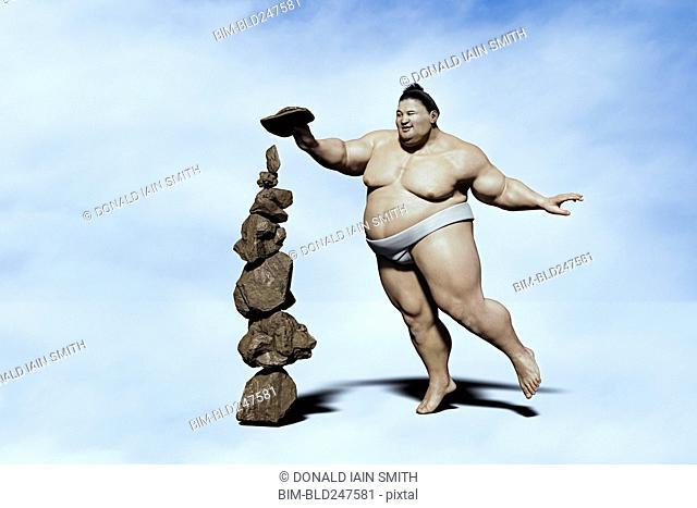 Sumo wrestler balancing pile of rocks