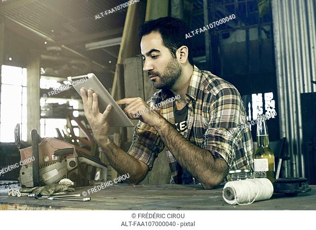 Man in workshop using digital tablet to access do-it-yourself repair instructions on internet