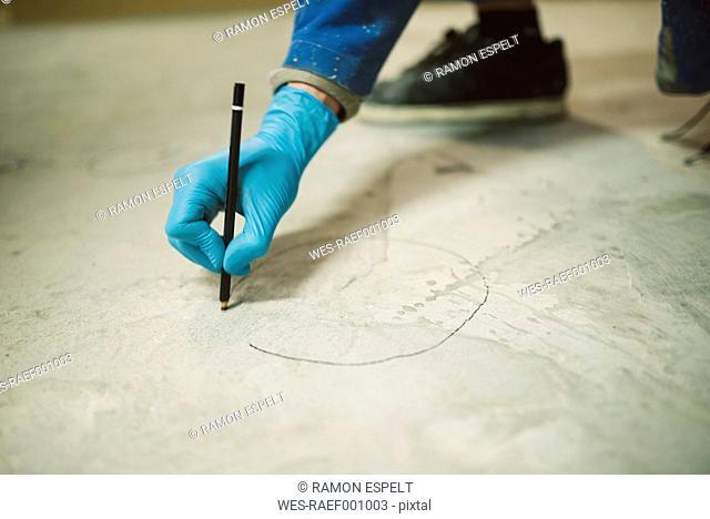 Bricklayer marking irregularities on floor screed