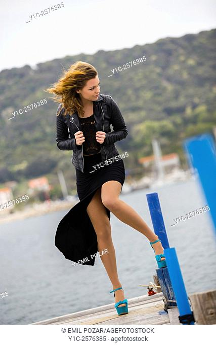 Young lady in Black dress fights strong wind