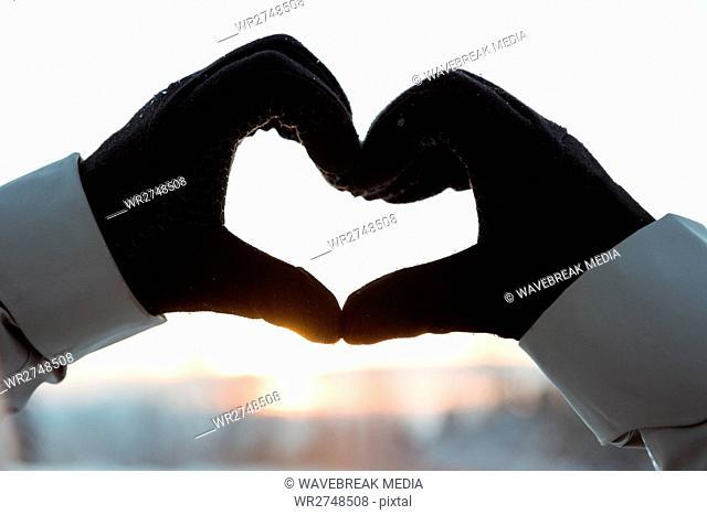 Hand making a heart shape against sunrise
