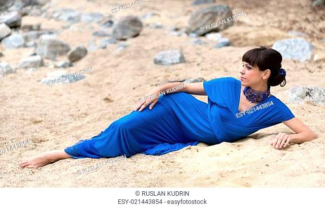 girl in a dress lying on the sand
