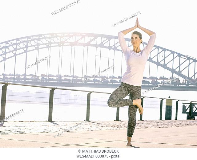Germany, Cologne, young woman practicing yoga, tree position
