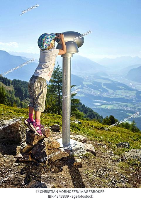 Little girl standing on tiptoes, looking through a telescope, Zirbenweg, Patscherkofel, Innsbruck, Tyrol, Austria