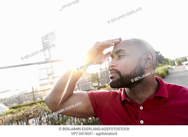 Man looking at view, shielding eyes. Frankfrut, Germany
