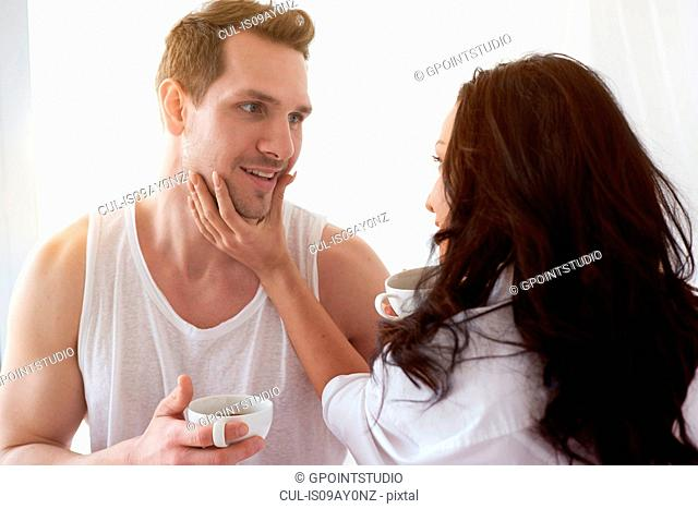 Romantic young couple face to face on bed