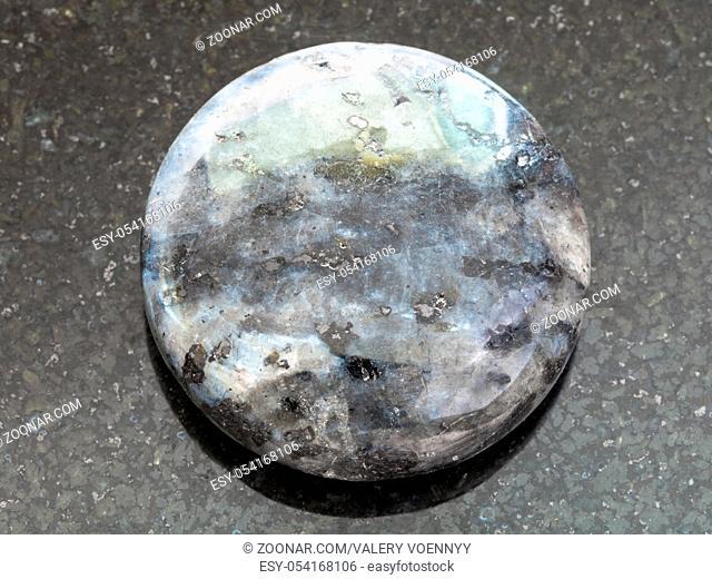 macro shooting of natural mineral rock specimen - bead from gray Labradorite gemstone on dark granite background