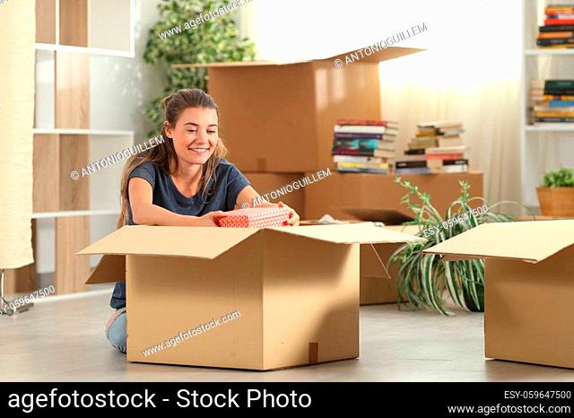 Happy girl unpacking boxes moving to new home sitting on the floor in the living room