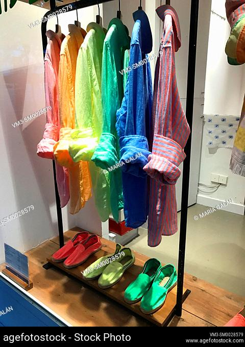 Color shirts matching with color espadrilles in a shop window. Madrid, Spain