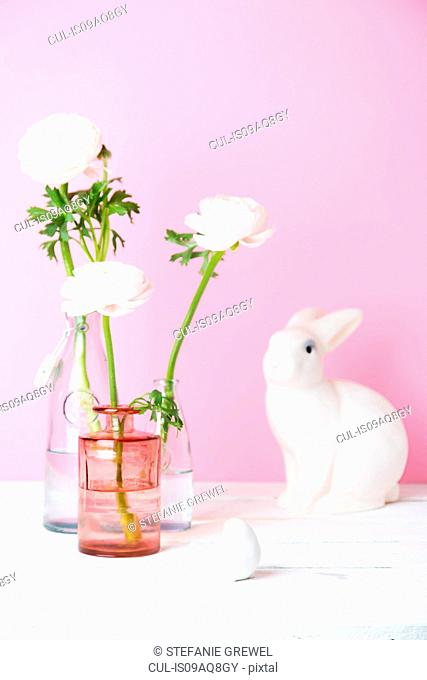 Still life of cut flowers in bottles, white Easter bunny and bird